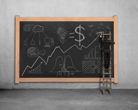 Man on ladder drawing business concept doodles on blackboard photo