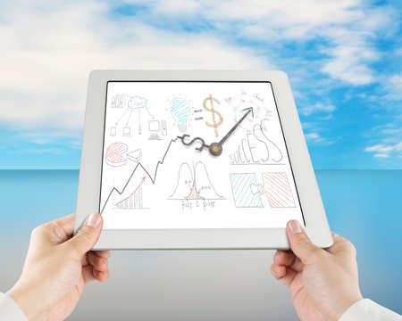 Hand holding tablet with business concept doodles and clock hands sky photo