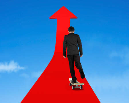 businessman money skateboarding on red arrow in sky photo