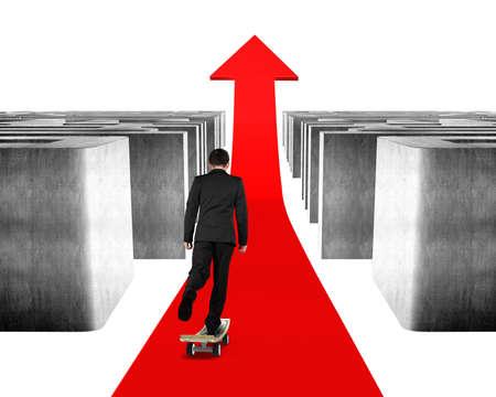 Businessman skateboarding through concrete maze on red arrow photo