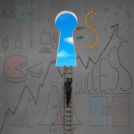 Climbing to key shape door with business doodles on concrete wall photo