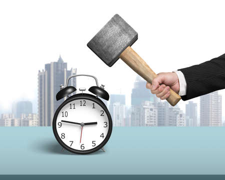 hitting alarm clock with hammer on table city view background photo