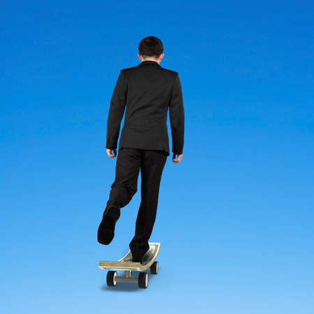 Businessman skateboarding on money skateboard in blue background photo