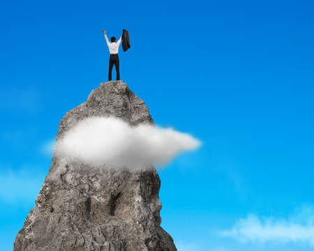 jubilation: Businessman cheering on top of rocky mountain with blue sky