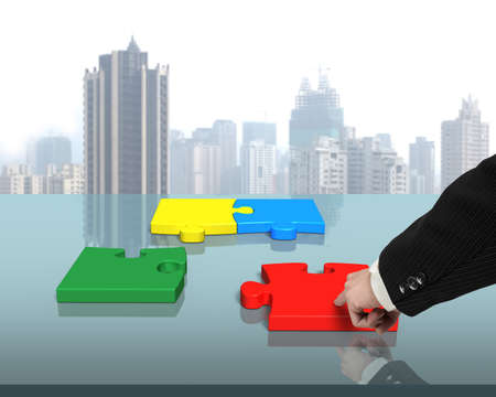 Man Assembling four puzzles on table in office photo