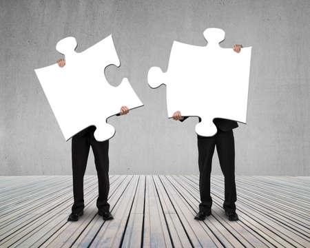 木製の床に接続する 2 つのパズルを保持しているビジネスマン 写真素材