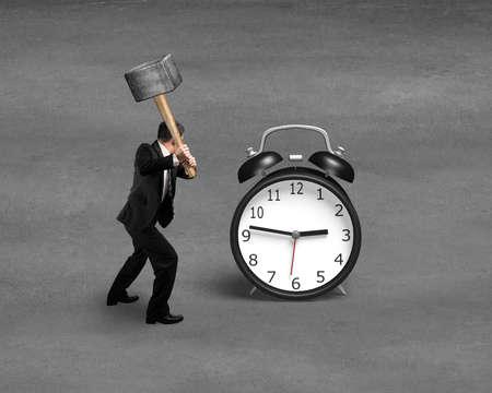 Businessman using sledge hammer to hit alarm clock photo