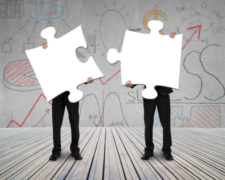Two people holding puzzles to connect business doodles  photo