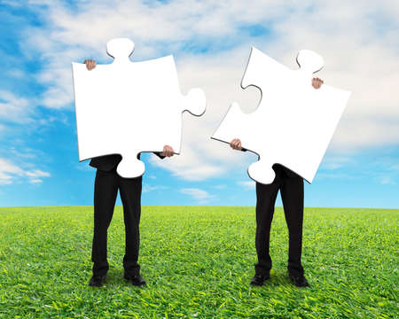 Two men holding blank puzzles on grass ground with blue sky photo
