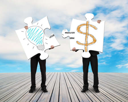 copartnership: Two businessmen assembling puzzles for Idea is Money doodles blue sky  Stock Photo