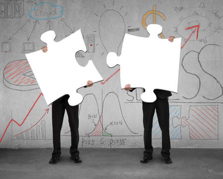 Two men assembling puzzles with business doodles on concrete wall photo
