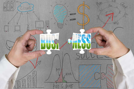 Assembling two puzzles for green business with doodles on concrete wall photo