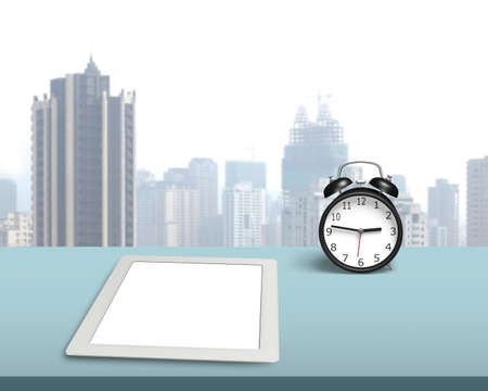 Blank tablet with retro alarm clock on desk in office photo