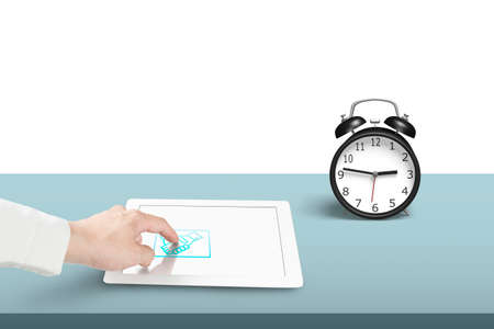 Touching hand shake icon on tablet with alarm clock photo