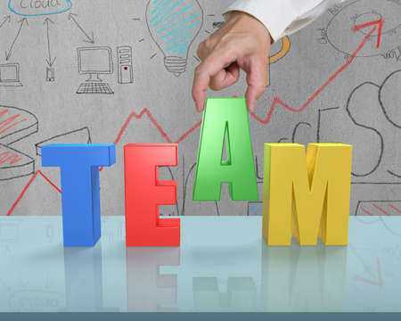 Putting A into TEAM on glass table in office photo