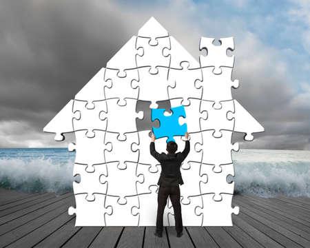Blauwe puzzel in huis vorm op houten pier met bewolkt en golf Stockfoto