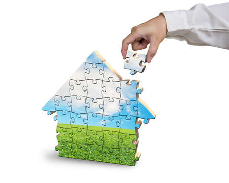 Assembling house shape puzzles in beautiful landscape in white background photo