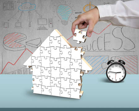 Assembling puzzles for house shape on desk in office photo