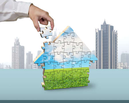 Assembling puzzles in house building shape in office photo