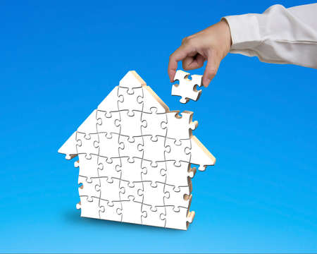Putting puzzle in house shape blue background photo