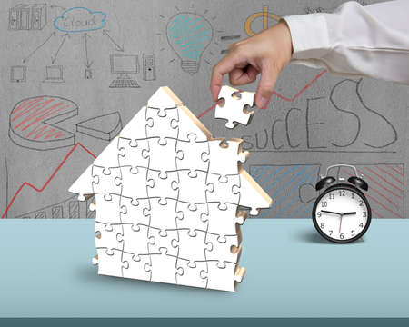 Finishing to assemble puzzles in house shape with doodles background photo