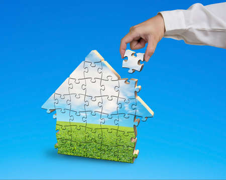 Assembling puzzles in house shape isolated in blue background photo