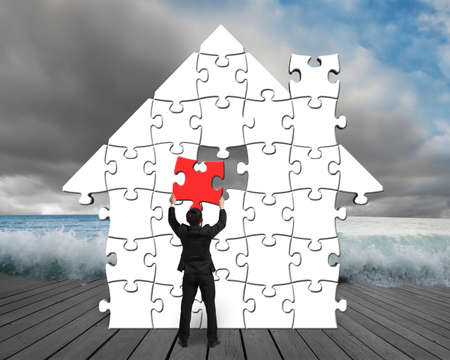 house flood: Assembling puzzles in house shape with flood and cloudy sky  Stock Photo
