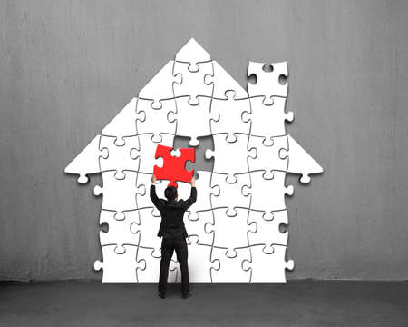 gather: Putting red puzzle into house shape on concrete wall Stock Photo