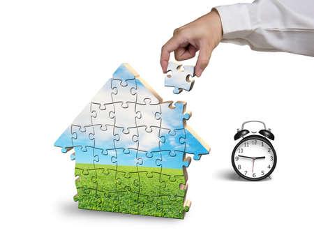 Finishing house shape puzzles assembling in white background photo