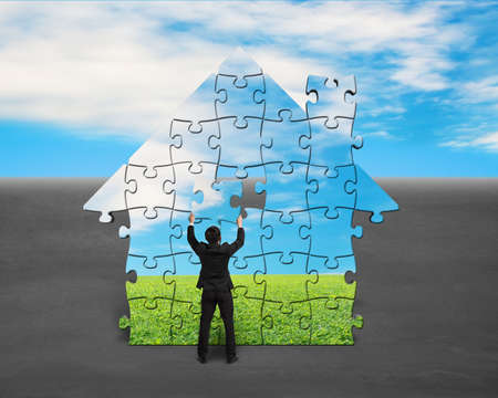 Assembling puzzles in house shape with blue sky background photo