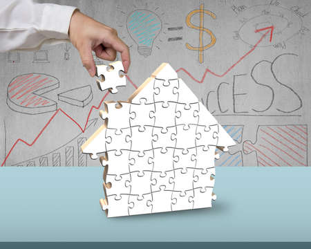 Assembling white puzzles in house shape with doodles on wall photo