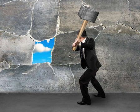 businessman destructing the wall with a large hammer