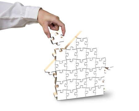 Finishing house shape puzzles isolated in white background photo