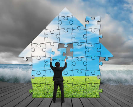 house flood: Finishing house shape puzzles assembling on pier with flood and cloudy sky Stock Photo