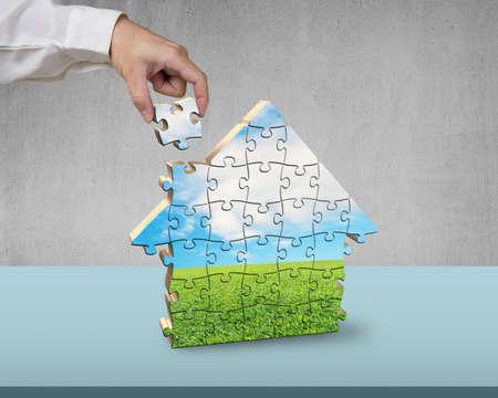 Assembling house shape puzzles on desk photo