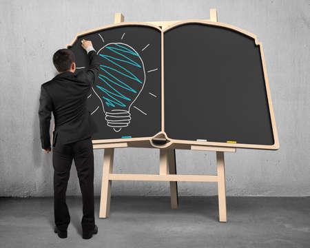 Businessman drawing lamp on book shape blackboard  photo