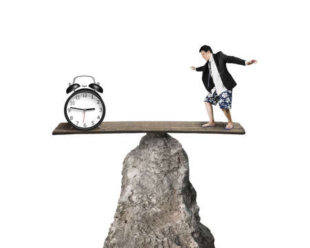 Man balancing against alarm clock at hilltop isolated in white background photo