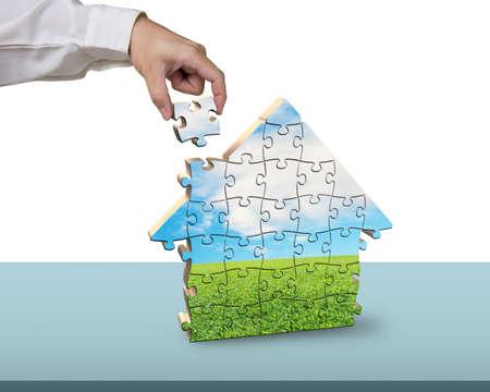 Finishing to assemble house shape puzzles with nature image photo