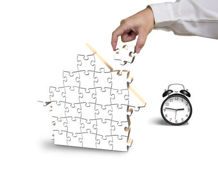 Finishing to assemble house shape puzzles with alarm clock isolated in white photo
