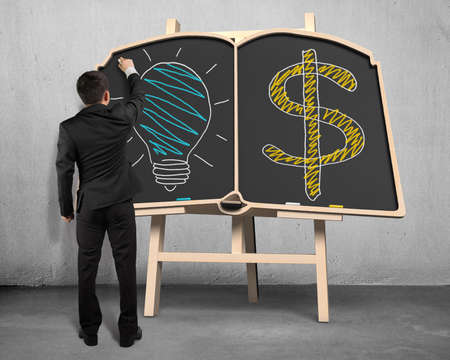 Businessman drawing glowing lamp and money symbol on blackboard photo
