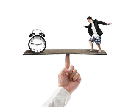 Man balancing against alarm clock isolated in white background photo
