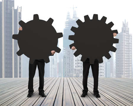 Holding two gears to connect on wooden floor with city view background photo