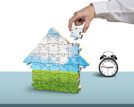 Assembling puzzles in house shape with alarm clock on desk Stock Photo