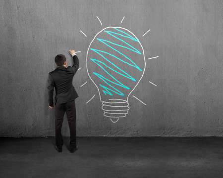Businessman standing and drawing lamp on concrete wall photo