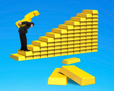 businessman carrying gold dollar up stack of bullion stairs isolated on blue background photo
