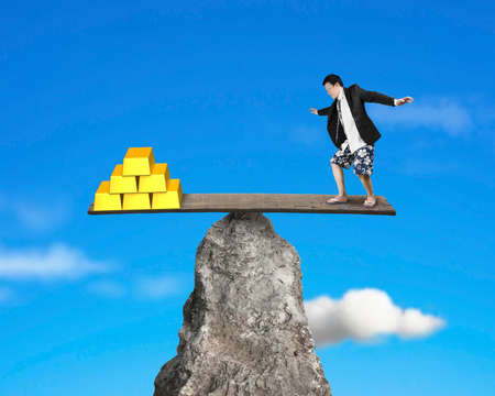rocky: person stands on rocky seesaw vs stack of gold with sky background Stock Photo