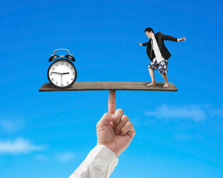 businessman standing on finger seesaw vs clock with sky background photo