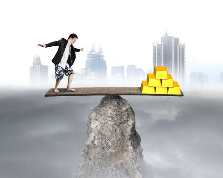 rocky: businessman stands on rocky seesaw vs stack of gold with city background