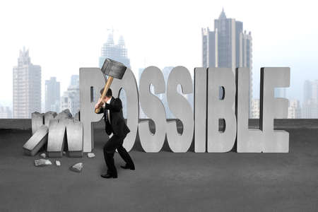 cement floor: businessman hold sledgehammer to smash impossible 3D concrete word on cement floor and city skyscraper background Stock Photo