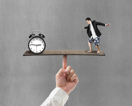 man standing on finger seesaw vs clock with gray background photo